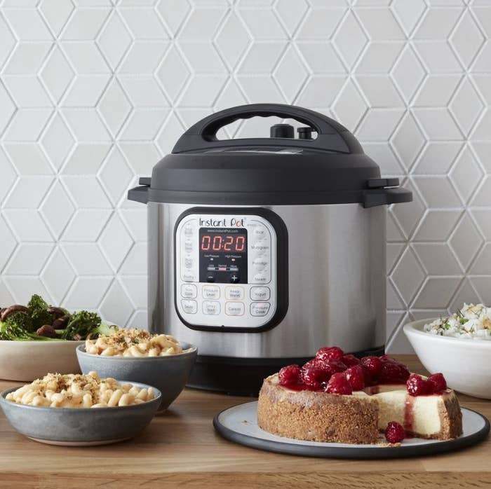 Silver instant pot with black lid in back of mac n cheese, broccoli,  and a cheesecake