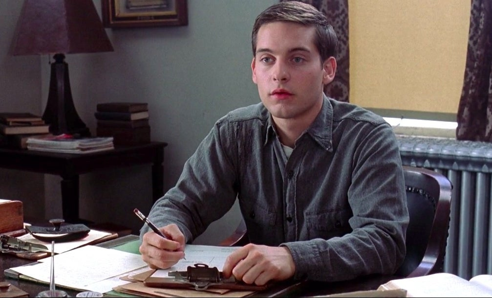 "tobey maguire sitting at a desk in ""the cider house rules"""