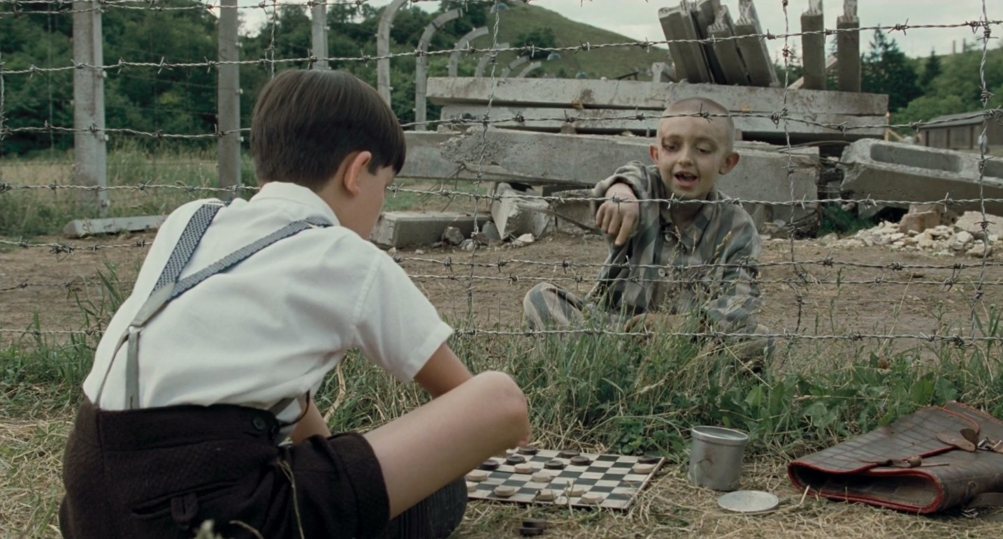 "a young german boy plays checkers with a young jewish boy at the edge of a concentration camp in ""The boy in the striped pajamas"""