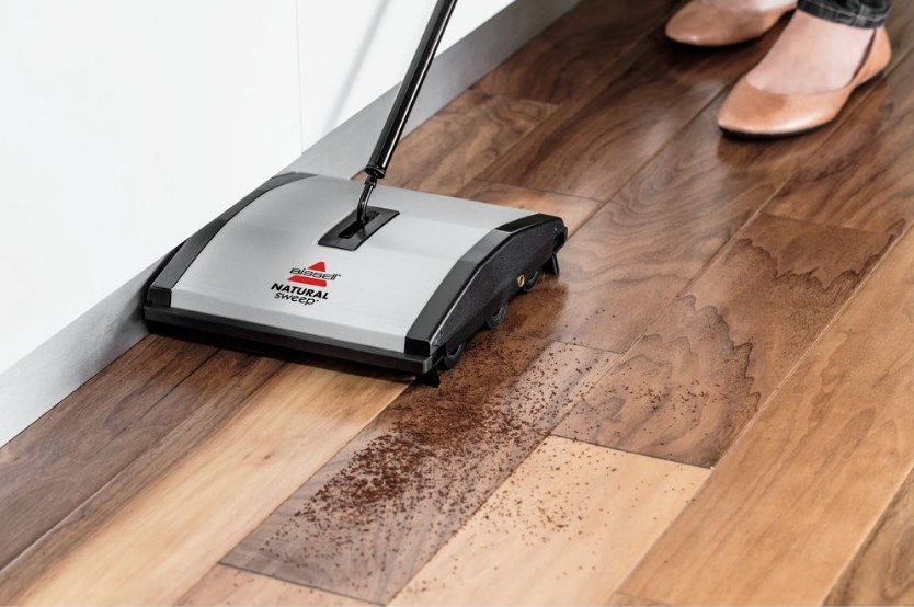 Silver bissell sweeper with black detailing sweeping dirt off wooden floor