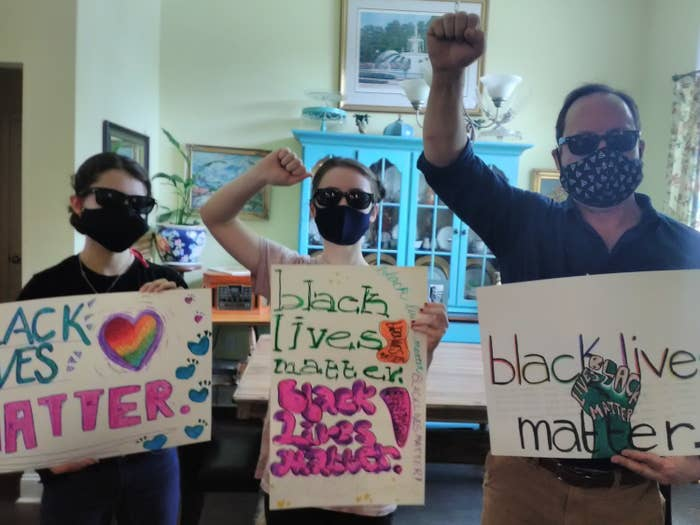 """Three white people holding """"black lives matter"""" signs"""