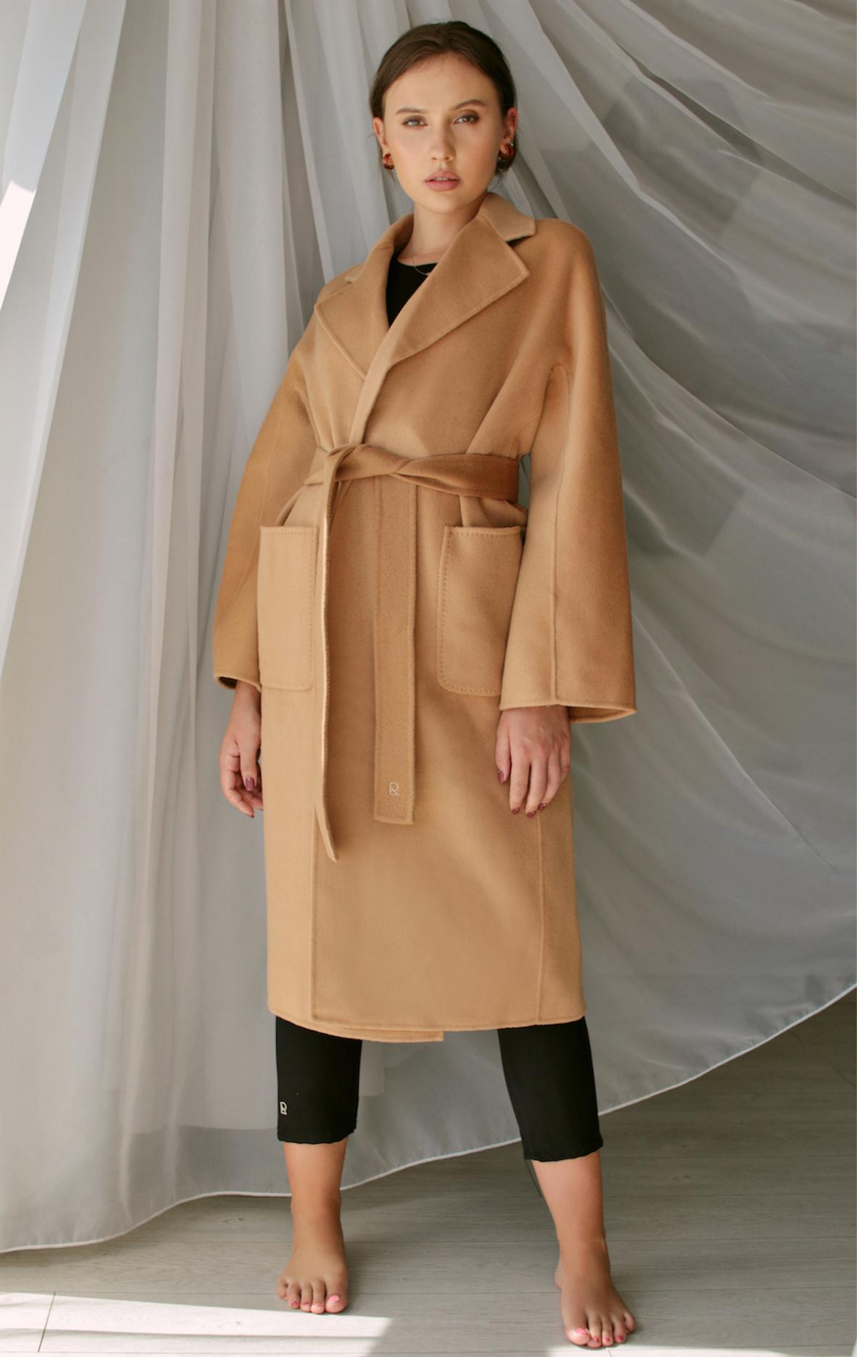 Model wearing the below knee-length coat with large pockets and tie waist in beige