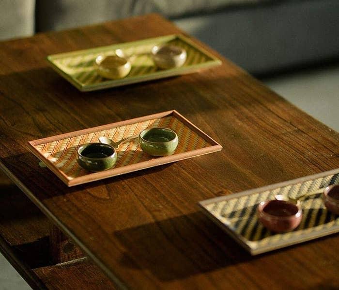 Three trays kept on a table holding small chutney bowls.