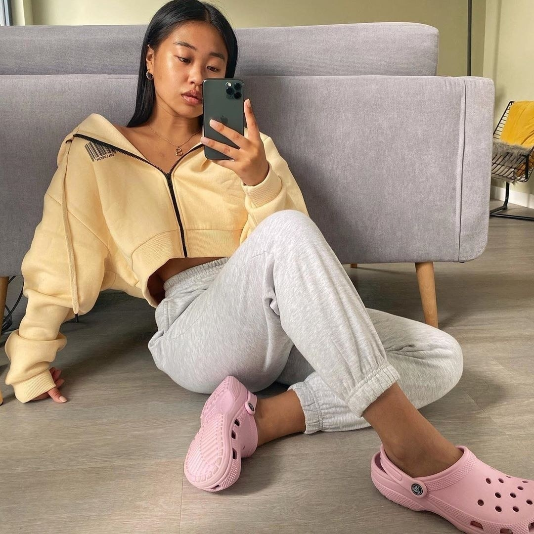 a model wearing pink crocs and cozy clothing