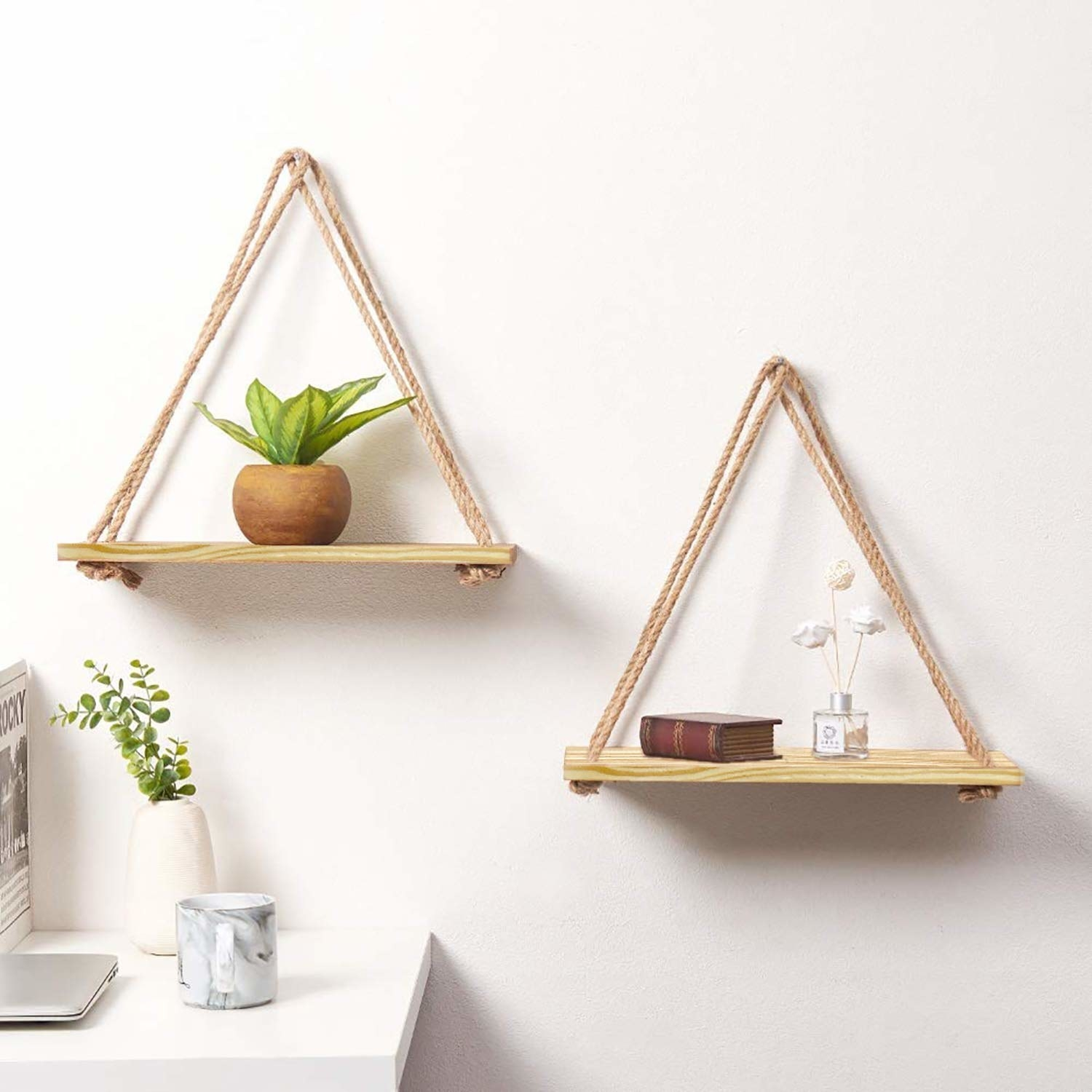 Two separate wooden slabs held together by ropes to form triangular hanging shelves.