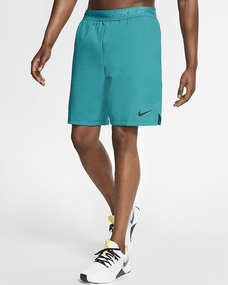 A model wearing the shorts in blue with Nike's Swoosh on the bottom left leg