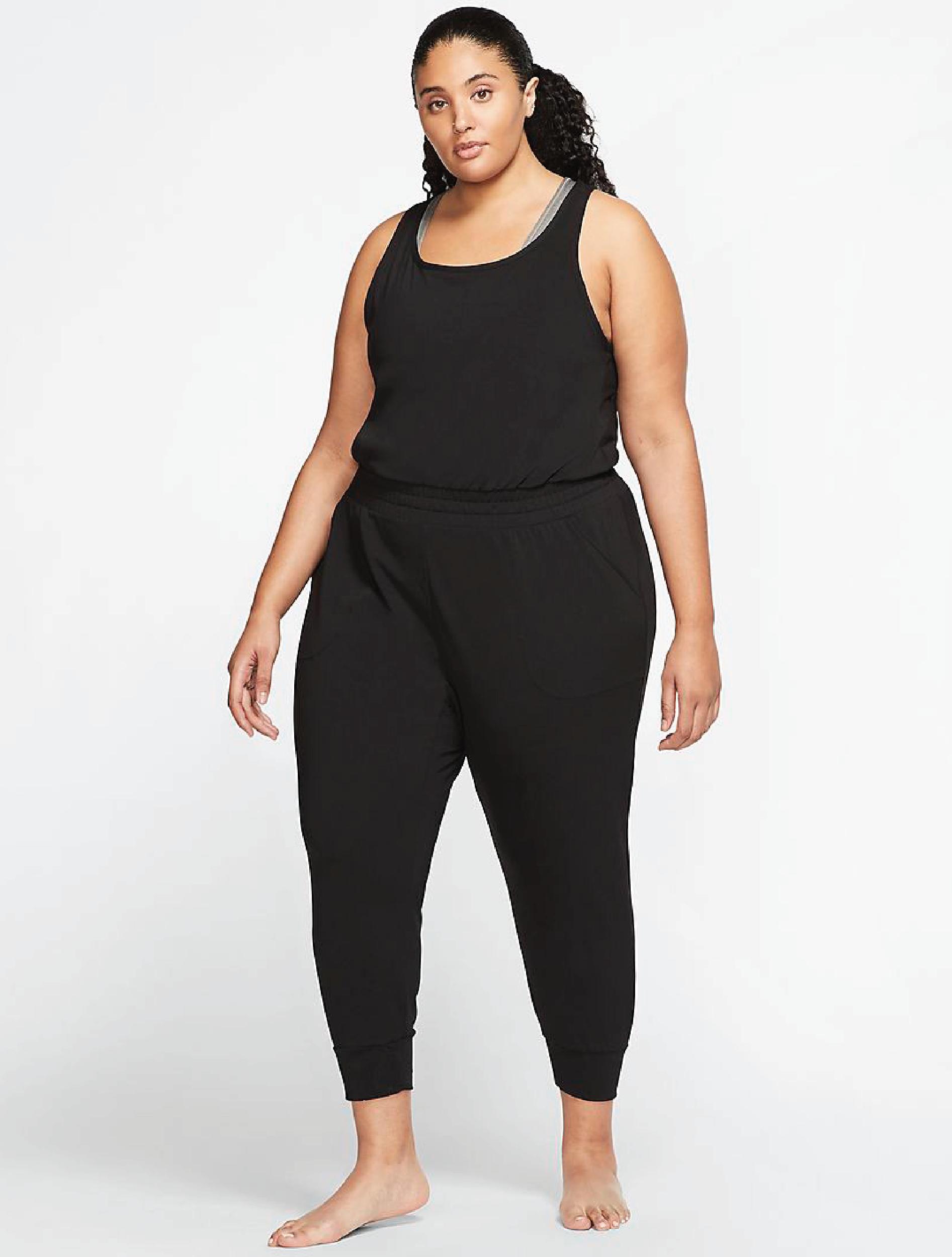 A plus sized model wearing the black jumpsuit
