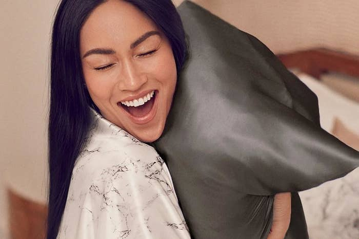 Model hugging a pillow with the silk pillowcase on it in black