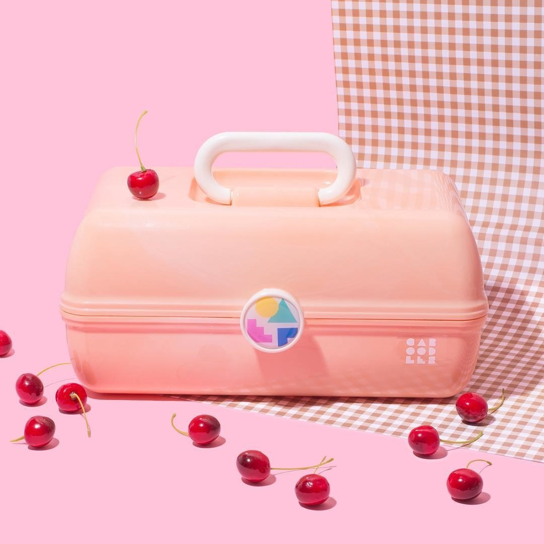 A large plastic makeup case with a handle on a plain background