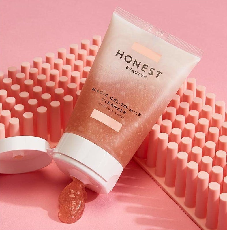 "a clear bottle with pink cleanser labeled ""Honest Beauty"""