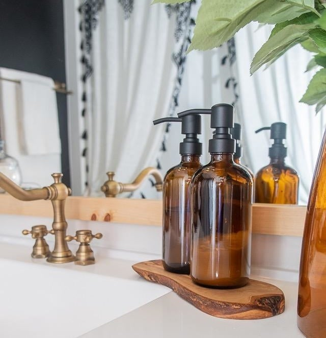 The bottles with black pumps on a bathroom counter