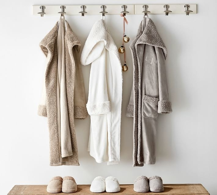 an oat colored, a white, and a grey plush robe hanging on a hook