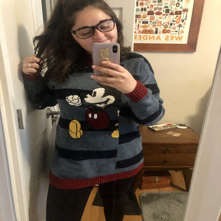 buzzfeed editor in the sweater that has light blue and navy stripes and red edges with an image of mickey running on the middle