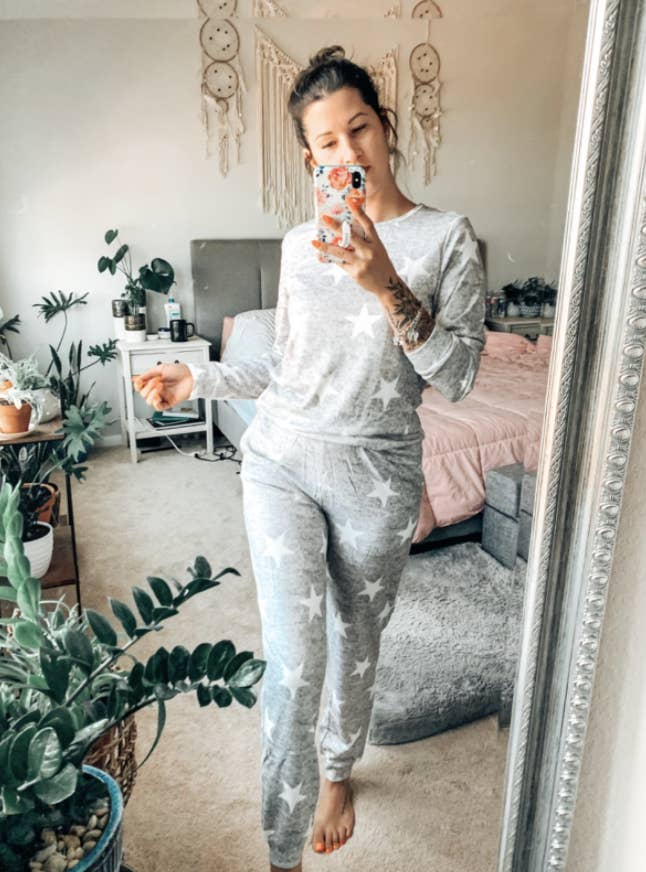 a reviewer in a long sleeve and pants set in grey with white stars on it