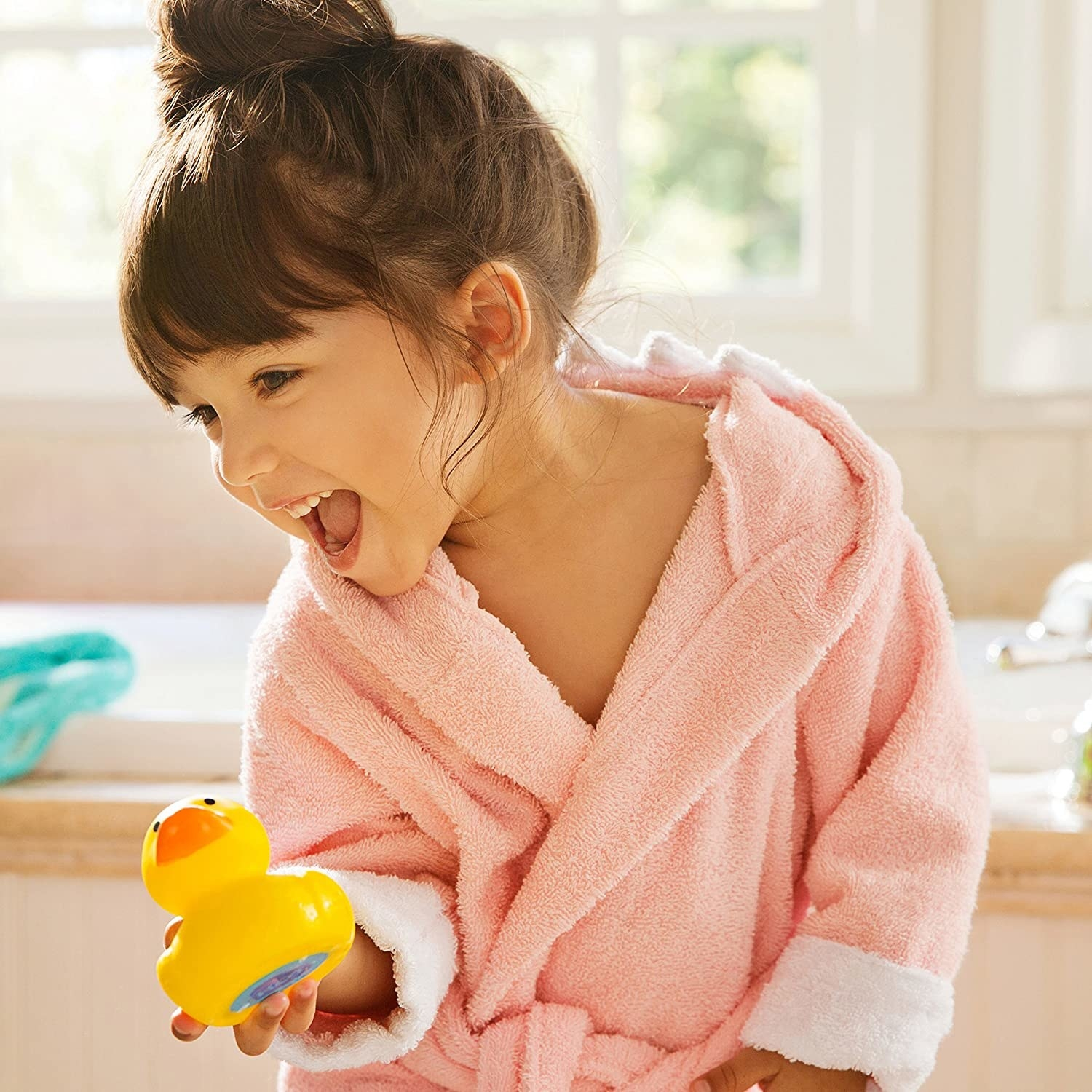 A small child holding a rubber duck toy