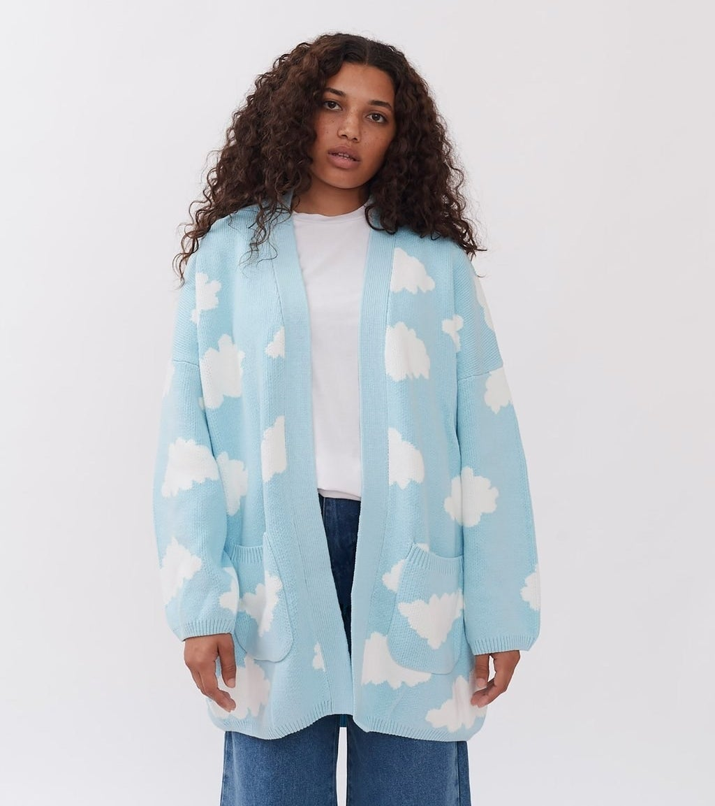 a model wearing a light blue cardigan covered in white clouds