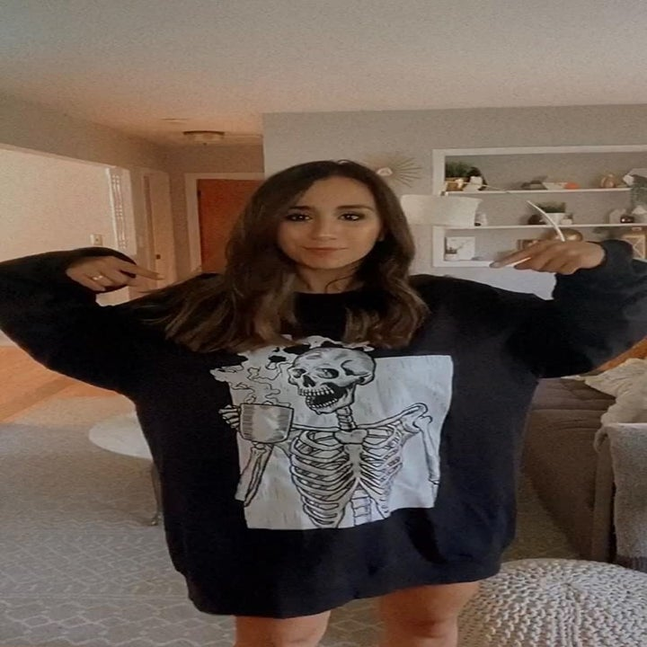 a reviewer in an oversized black sweatshirt with a white graphic of a skeleton drinking coffee