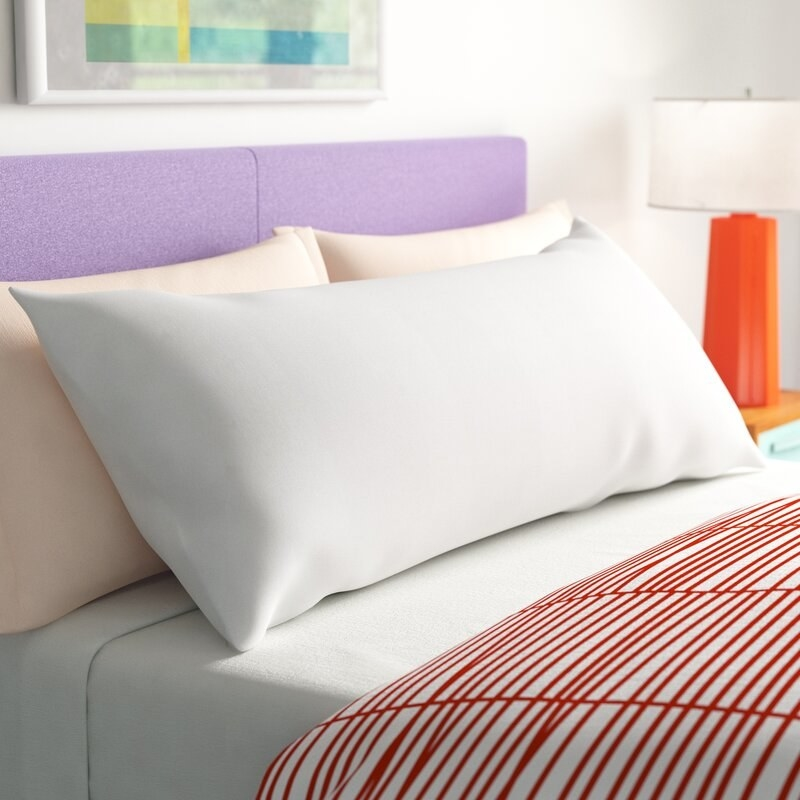 The body pillow, which is shaped like a standard pillow, but stretches the width of an entire bed
