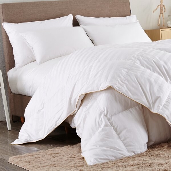 The comforter, which is white with a light striped pattern woven into the fabric