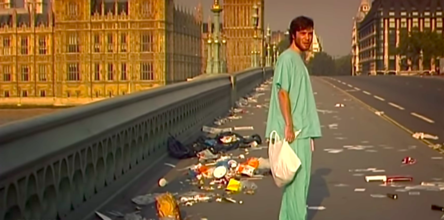 Cillian Murphy in scrubs, carrying a plastic bag, and standing on a deserted, trash-filled bridge in 28 Days Later