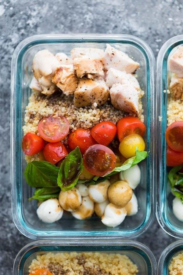 Glass containers filled with quinoa, mozzarella balls, tomato, chicken, and basil.