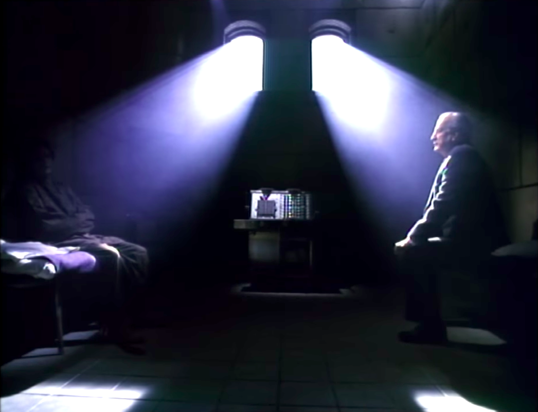 Jason Miller and George C. Scott talking in a cell in The Exorcist 3