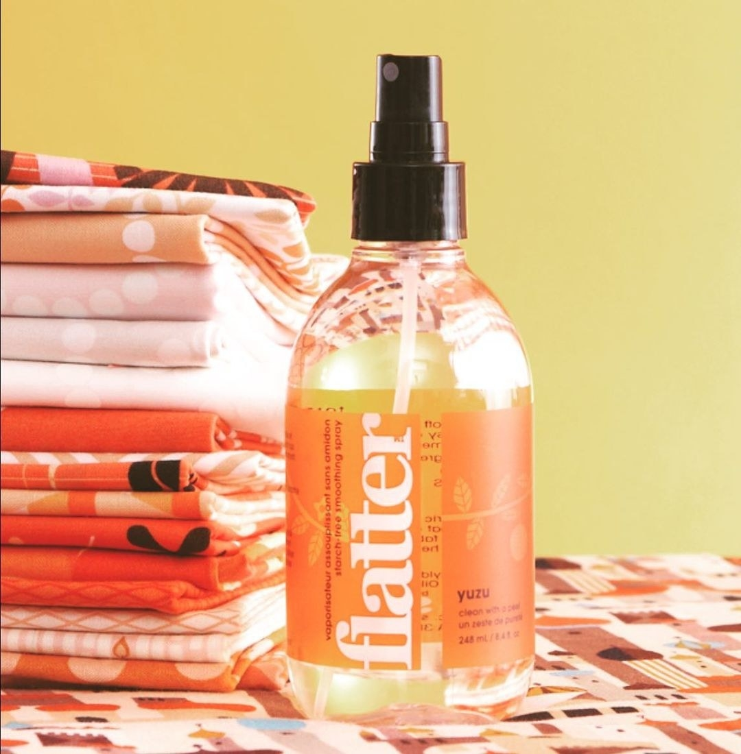 A bottle of spray next to folded linens