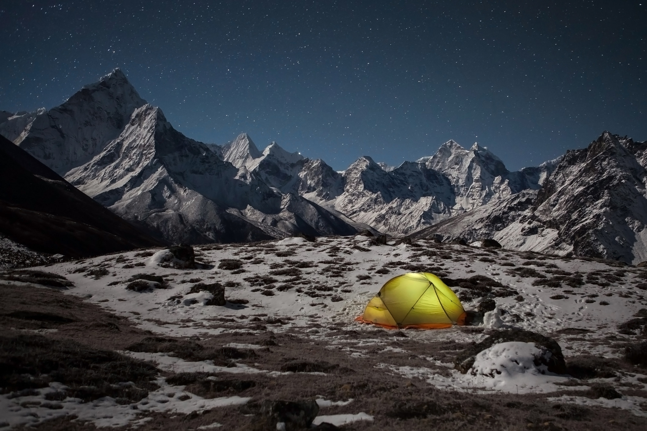 A glowing tent set up under a starry sky, surrounded by snowy mountains