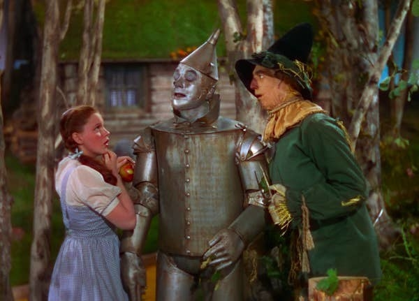 "dorothy, the tin man, and the scarecrow talk to each other in ""the wizard of oz"""
