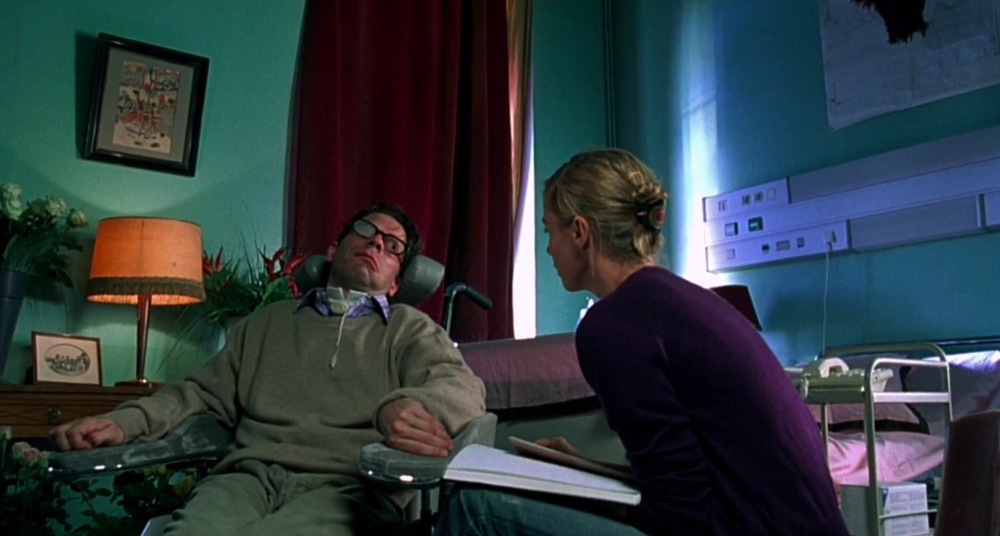 "Mathieu Amalric in a wheelchair talking to a woman in purple in ""the diving bell and the butterfly"""