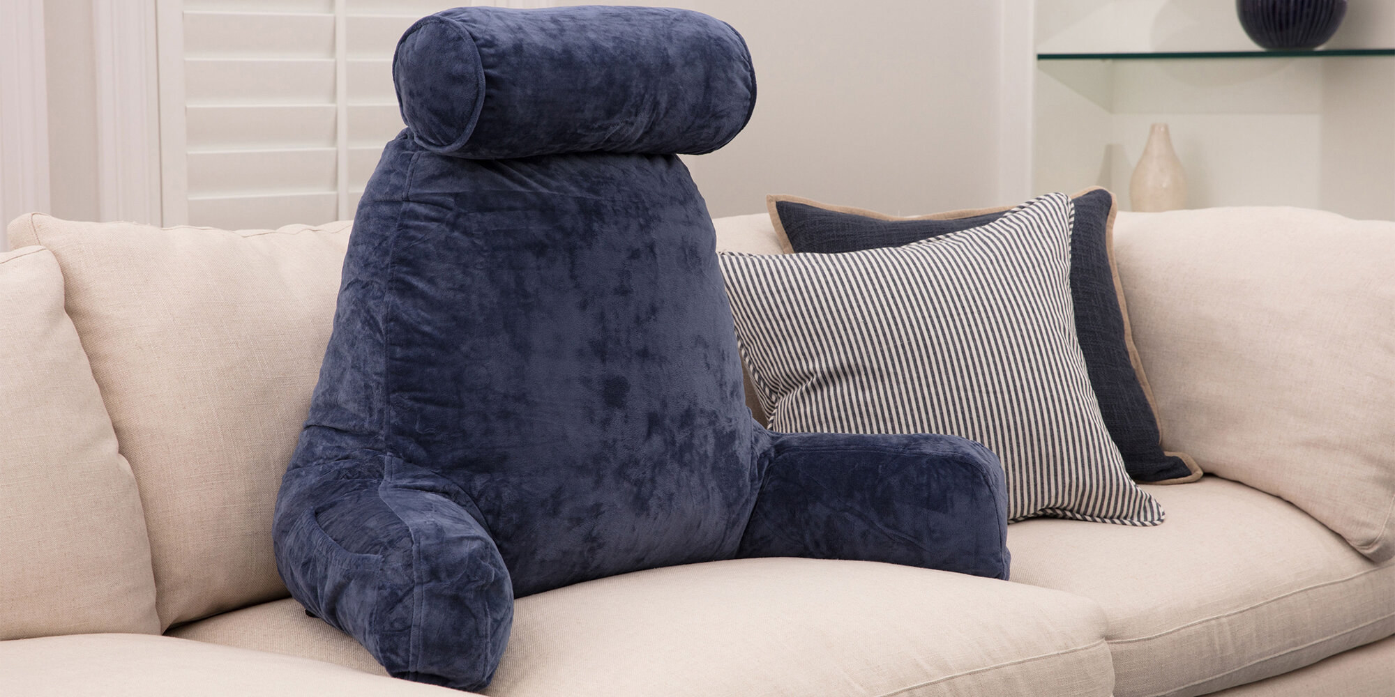 The pillow, which has a back support area, two arms that jut out from the bottom, and a cylindrical neck pillow