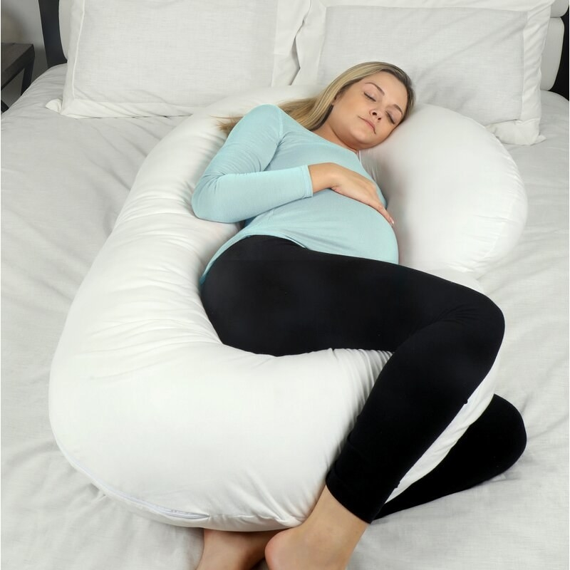 The pillow, which is C-shaped, with the ends going up through the knees and under the head area, respectively