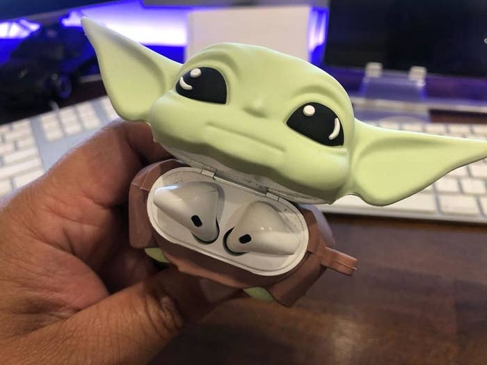 the baby yoda with the head tilted up to reveal airpods inside