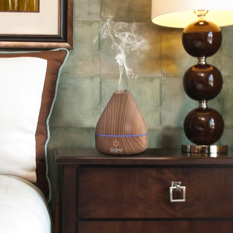 The diffuser in brown, emitting a small puff of steam and fitting easily on a bedside table