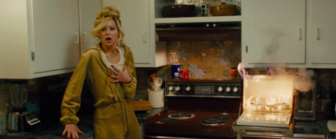 Jennifer Lawrence holding her chest and looking shocked while a microwave is on fire.