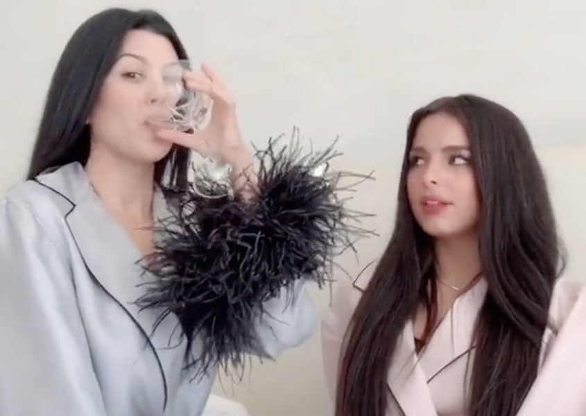 Kourtney sips from a martini glass while wearing purple feathered pajamas and Addison wears a matching pink outfit