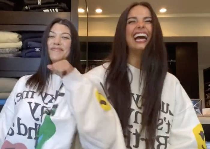 Addison Rae and Kourtney Kardashian smile while in the middle of a dance routine