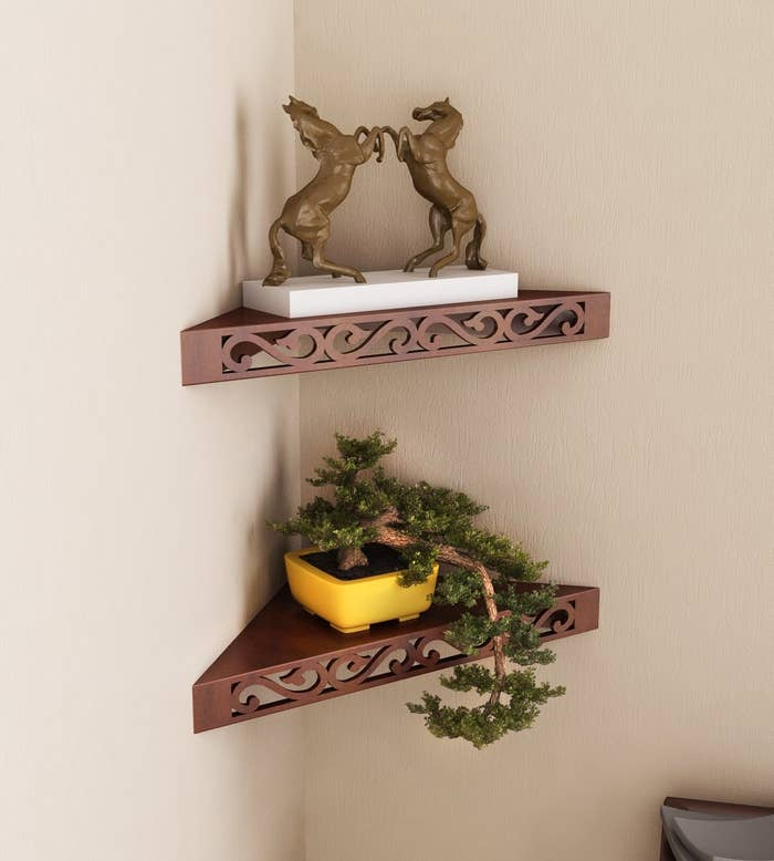 The corner shelf with detailing on the front panel, pictured with a plant and a showpiece.