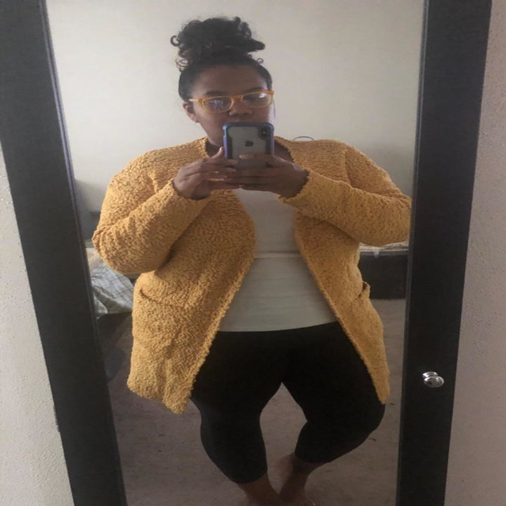 reviewer wearing the cardigan in yellow