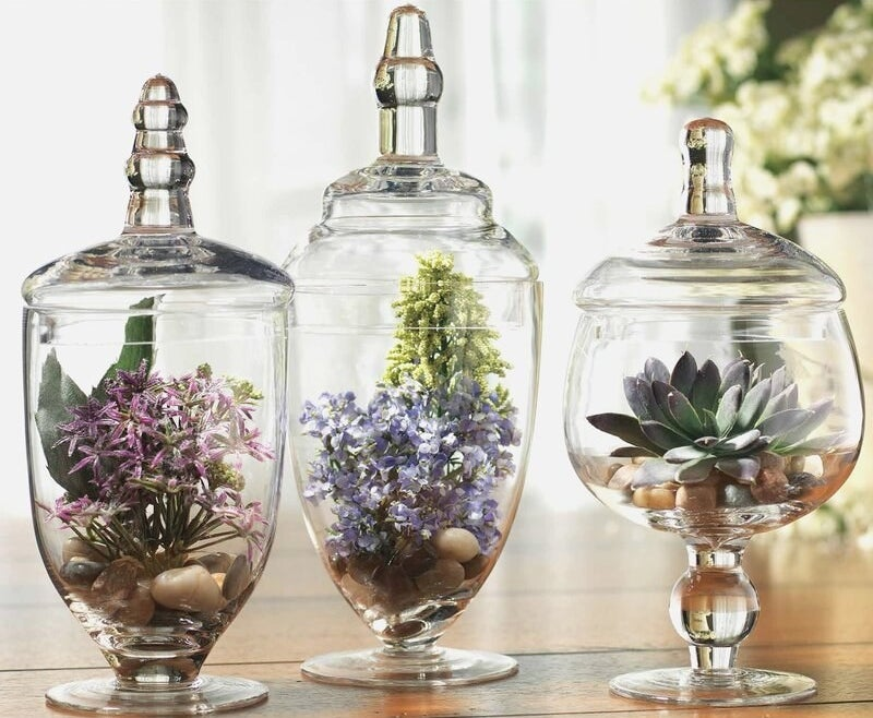 Apothecary jar set with colorful flowers inside