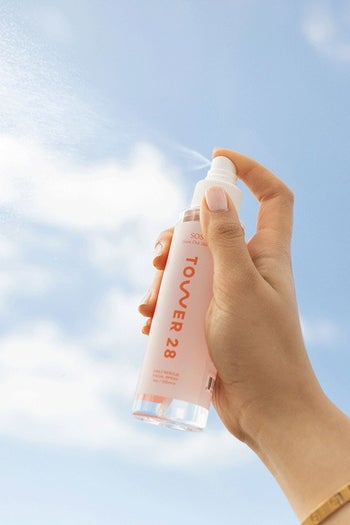 model holding the clear spray bottle with white cap labeled