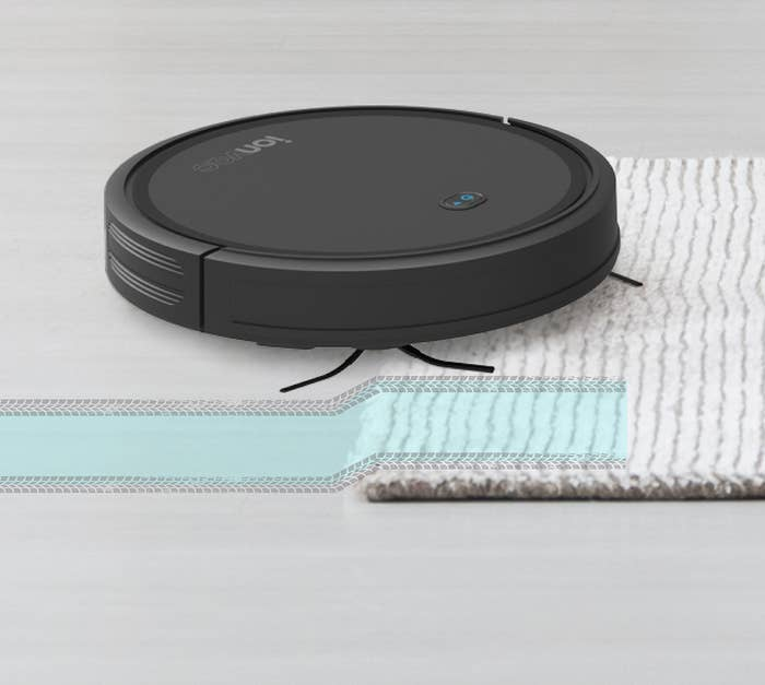 robot vacuum going over a rug on a hard floor