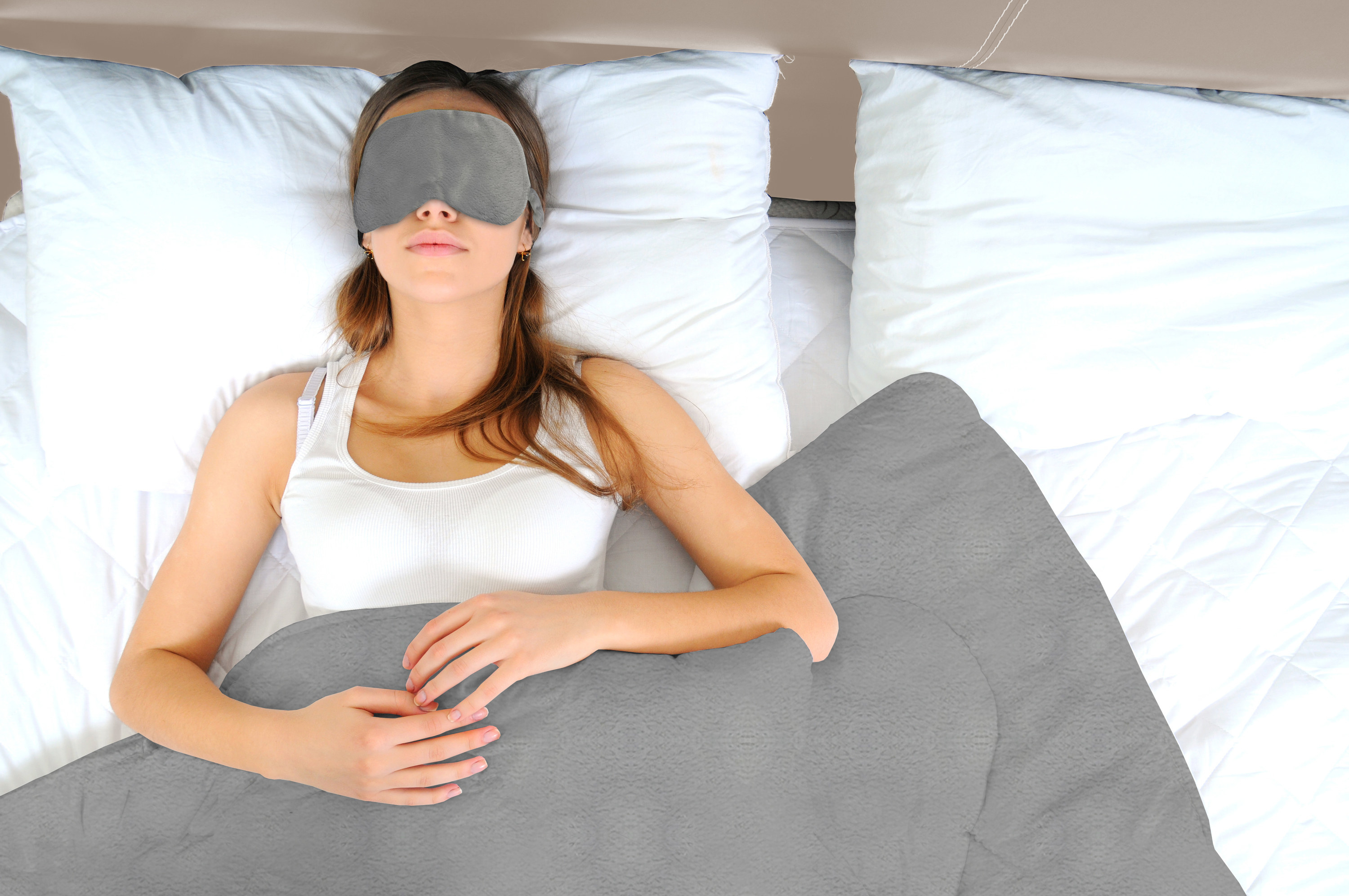 person wearing a sleeping eye mask and under a weighted blanket