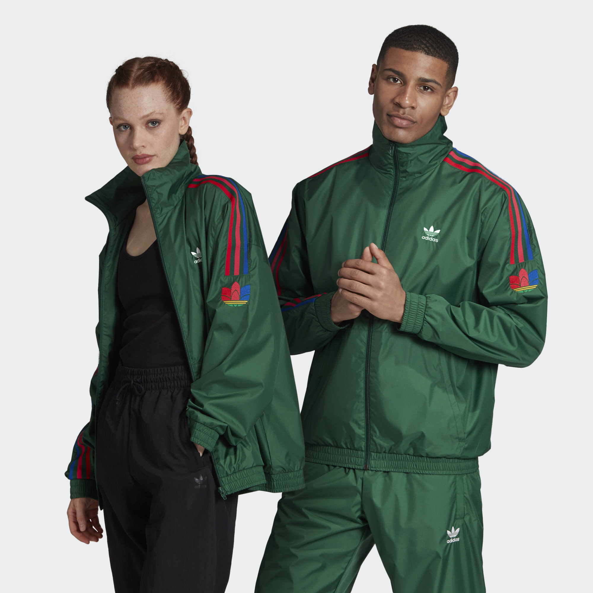 Two models wearing dark green 3-Stripes track jackets