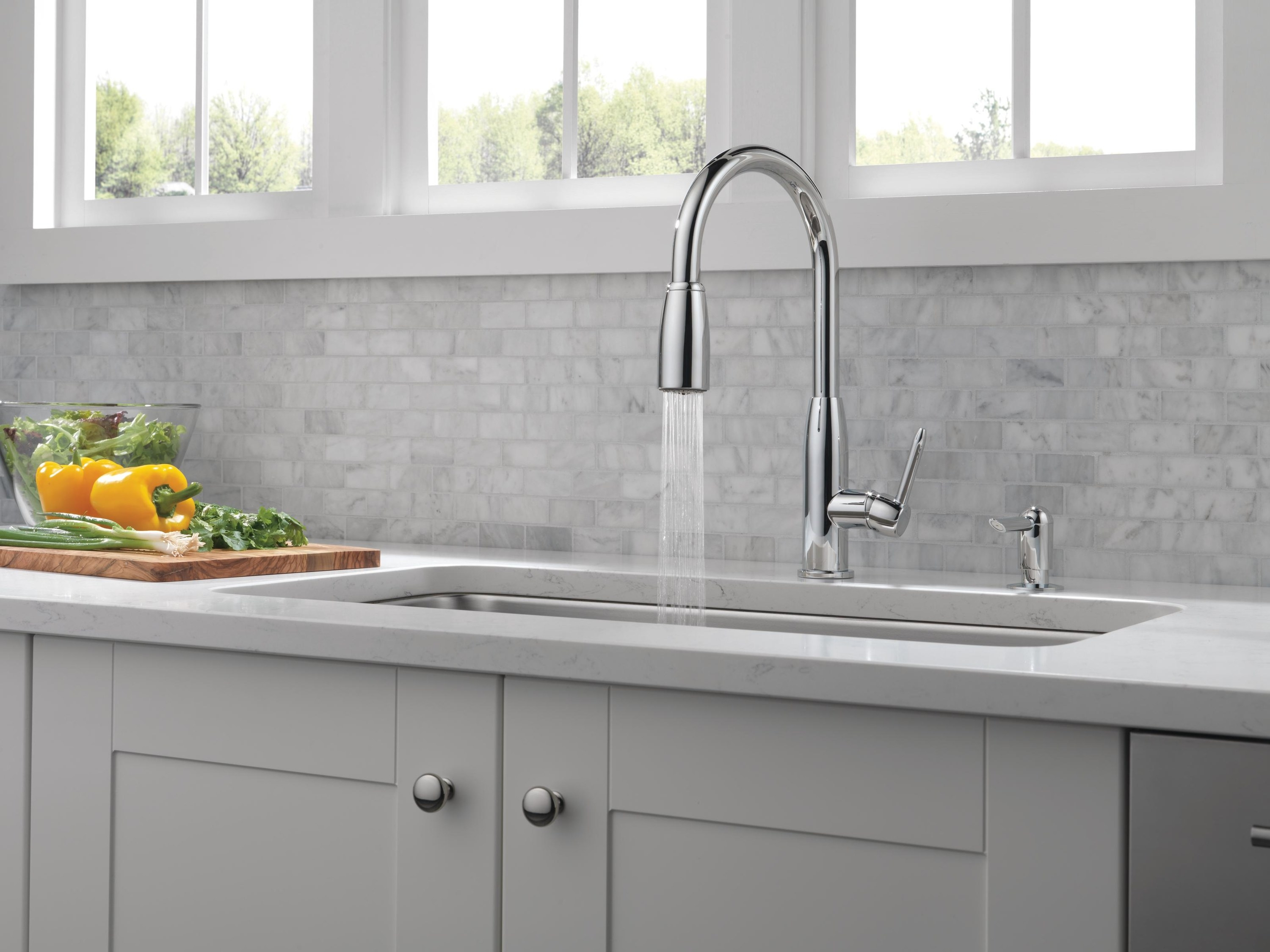 chrome single handle faucet with water flowing out of it