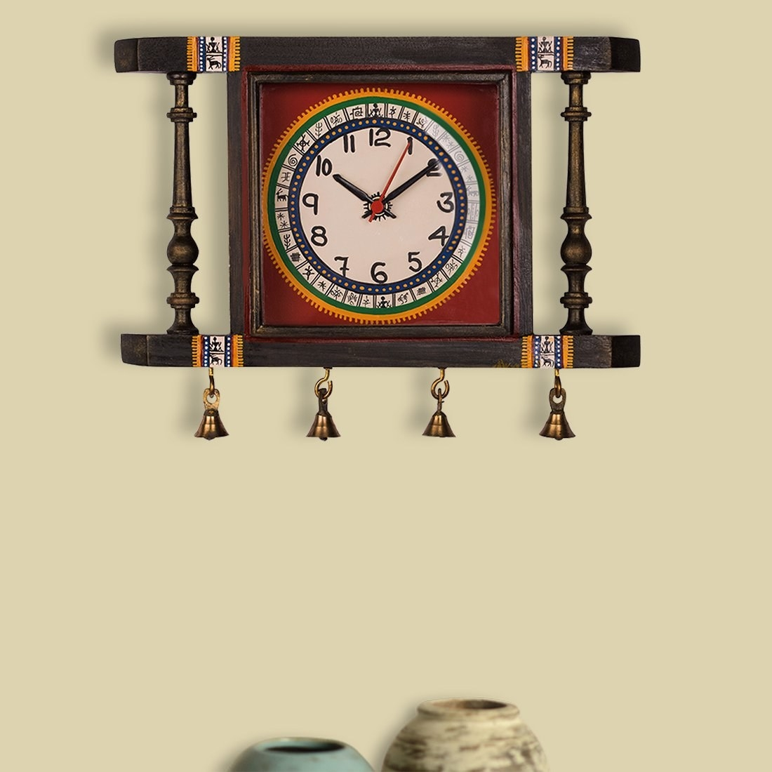 A square wooden clock with Warli paintings and small golden bells.