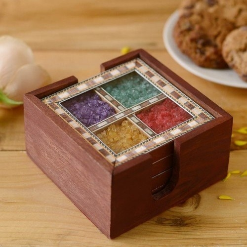 A set of square coasters filled with purple, tea;, yellow, and red gems.