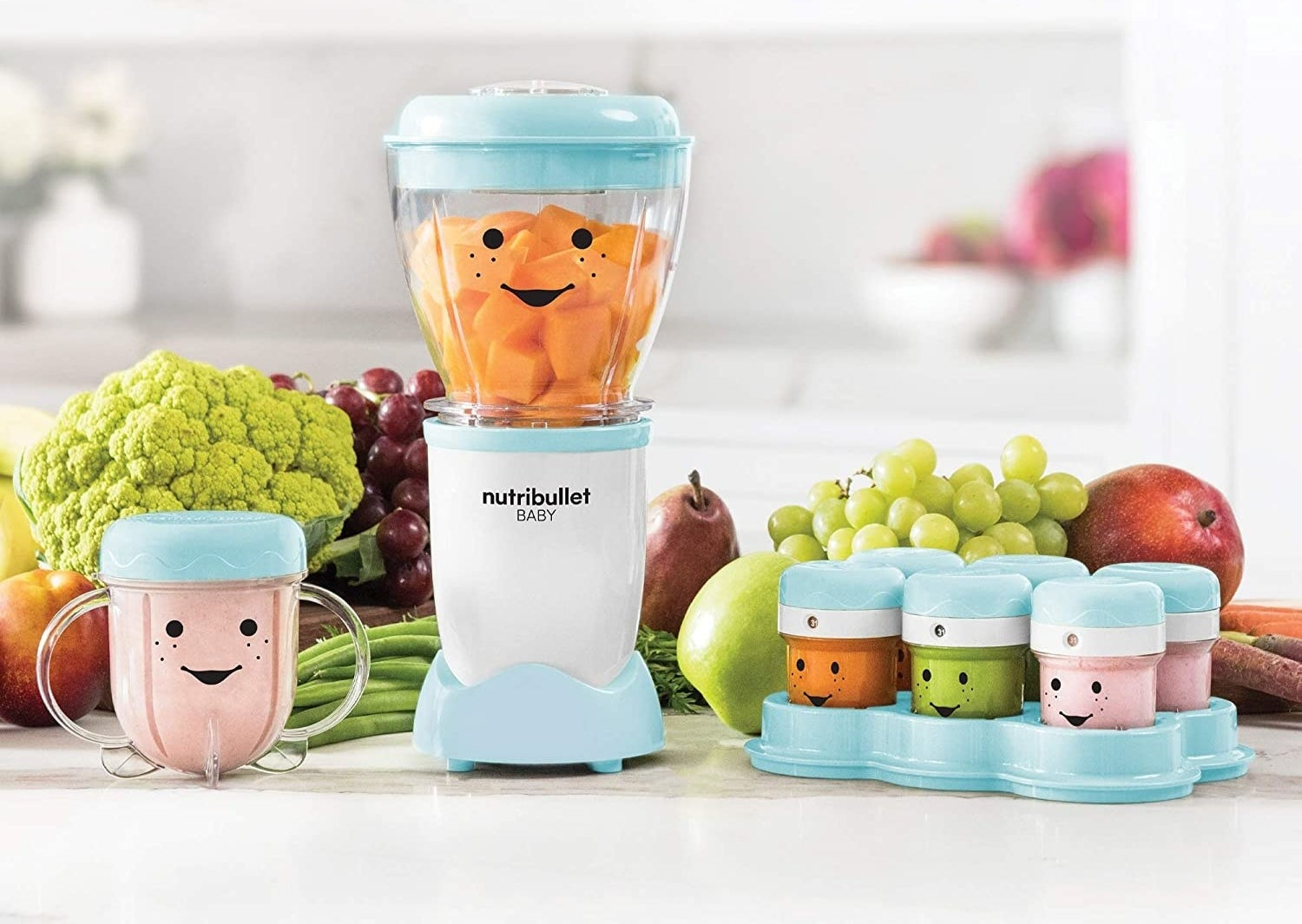 A small blender is sitting on a table with piles of fresh fruit and vegetables It has a cup with a lip next to it and a set of six small containers nearby
