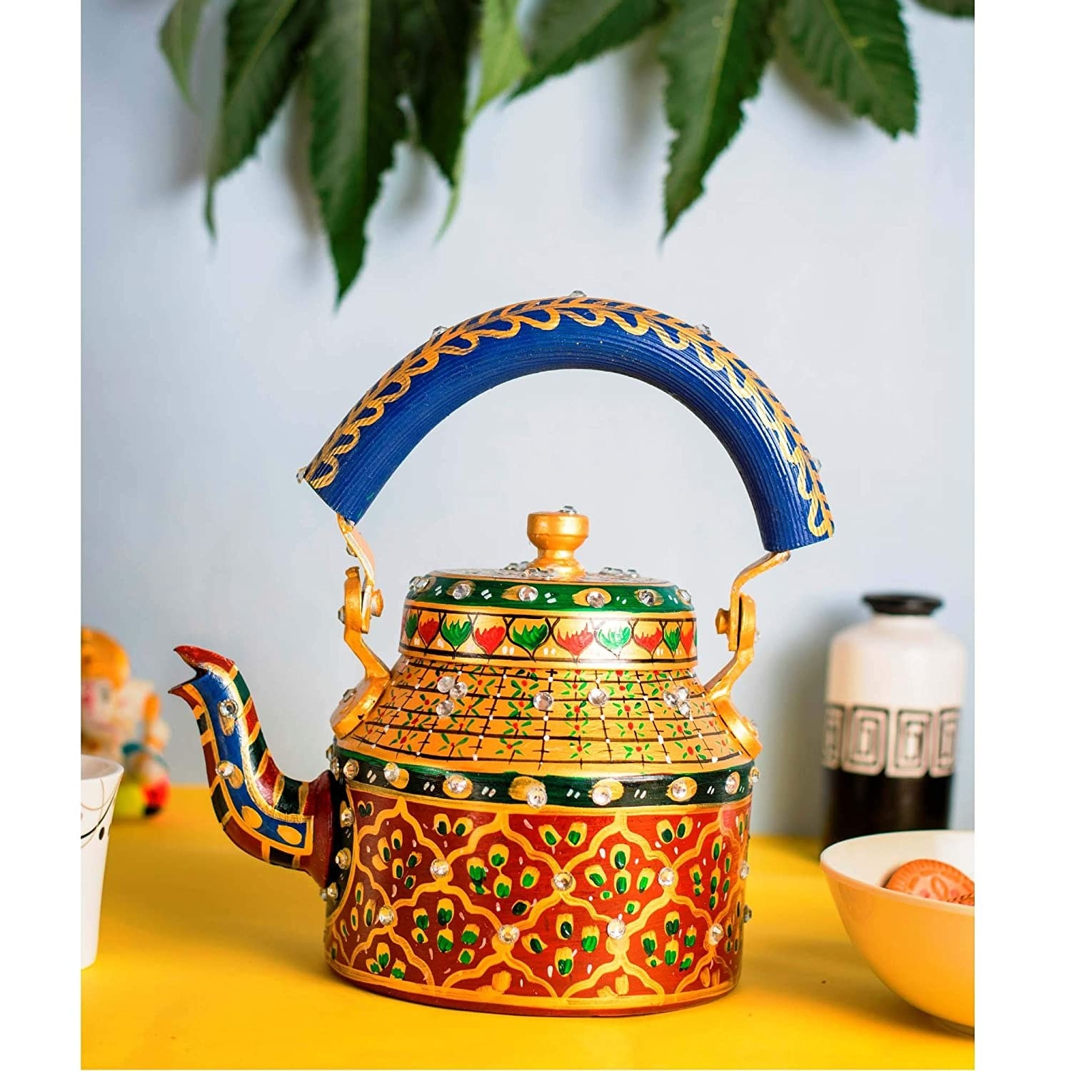 An aluminium kettle painted with an intricate design in shades of red, yellow, green, and royal blue.