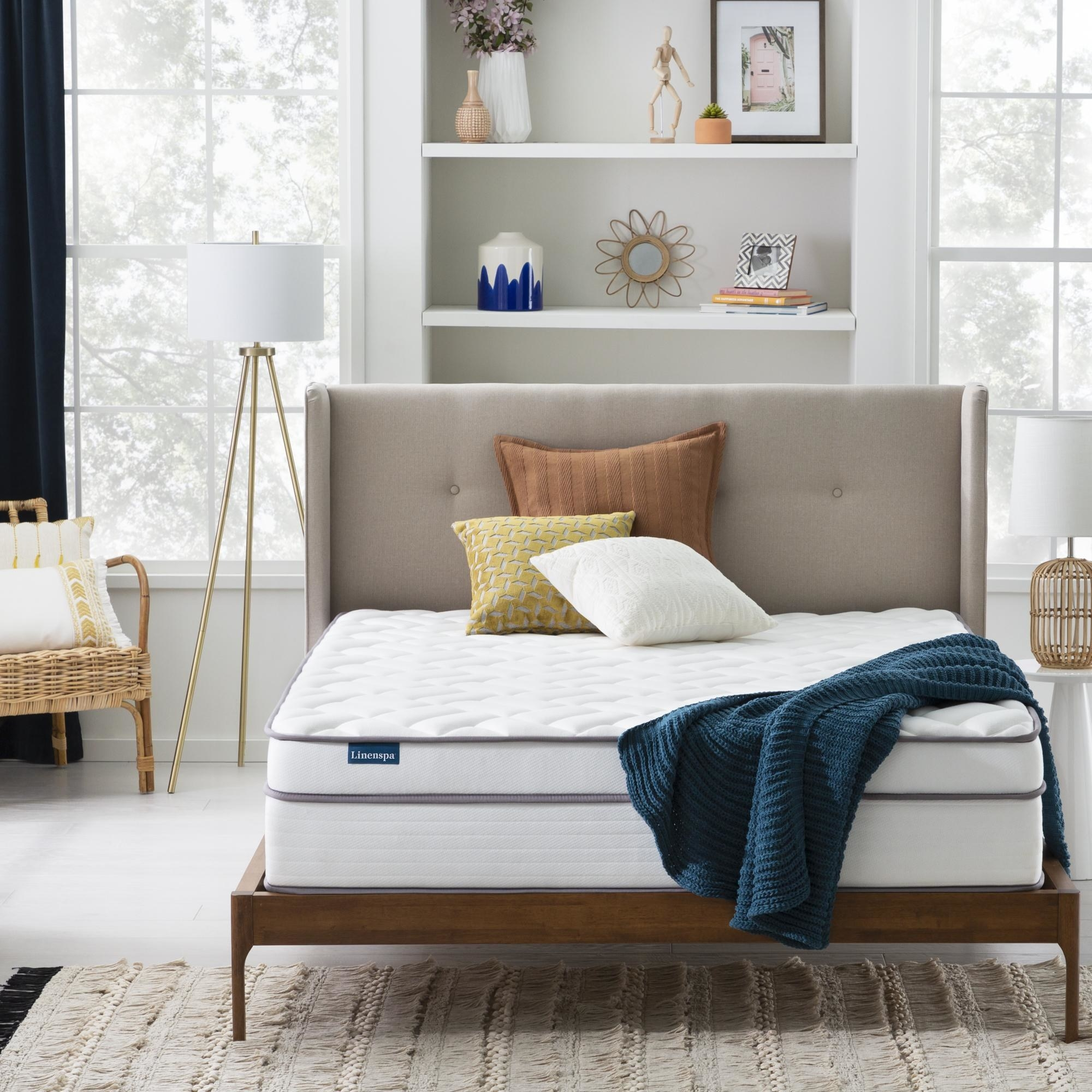 a mattress with two pillows and a blanket sitting on a bed frame in the middle of the room